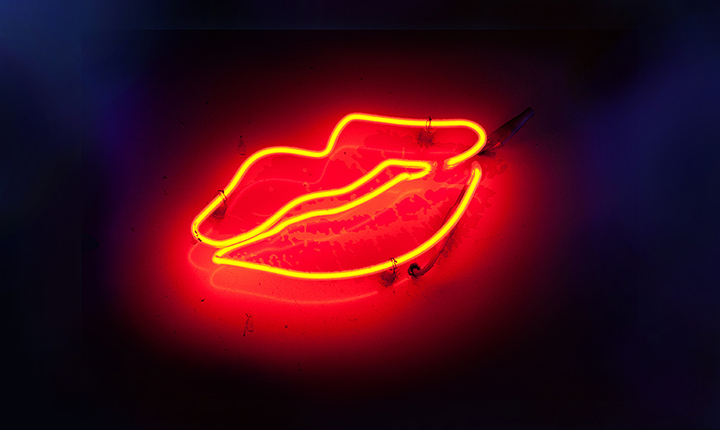 Red neon lights in the shape of lips glowing in front of a black background