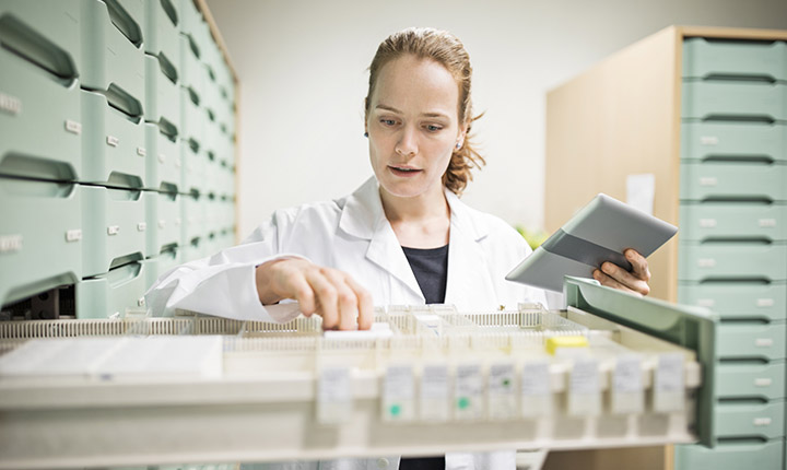 Woman in lab coat searching for medicines in a drawer