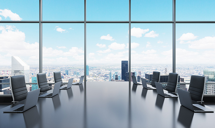 Large boardroom table equipped with laptops with panoramic city view in background
