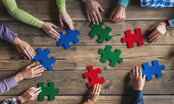 Hands around a wooden table holding red, blue and green puzzle pieces