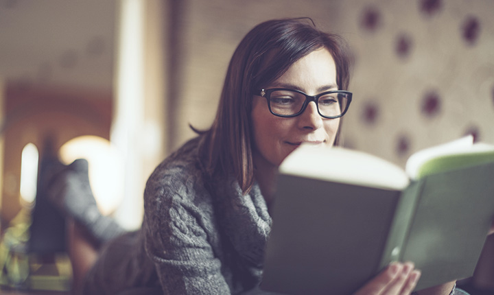 Woman wearing black glasses reading hardcover
