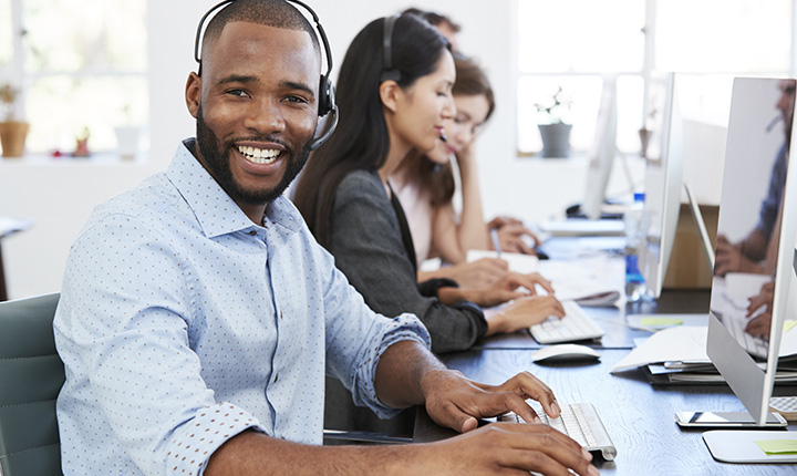 A diverse group of people at a call center smiling and answering phone calls.