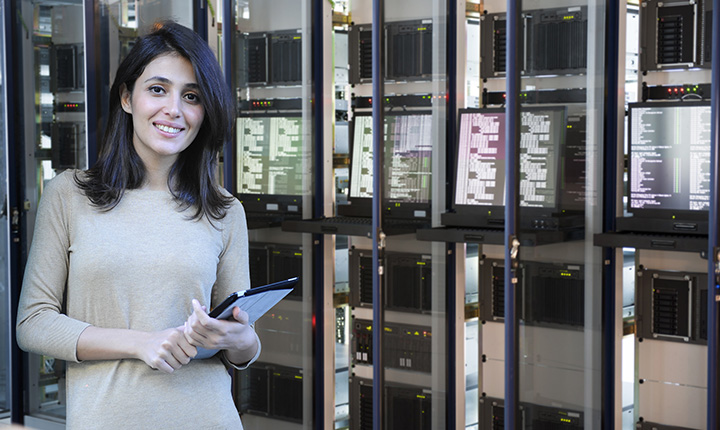Female IT engineer standing in front of a data center