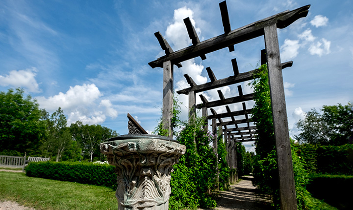 Stone sundial in front of hedge and pergola covered walking path