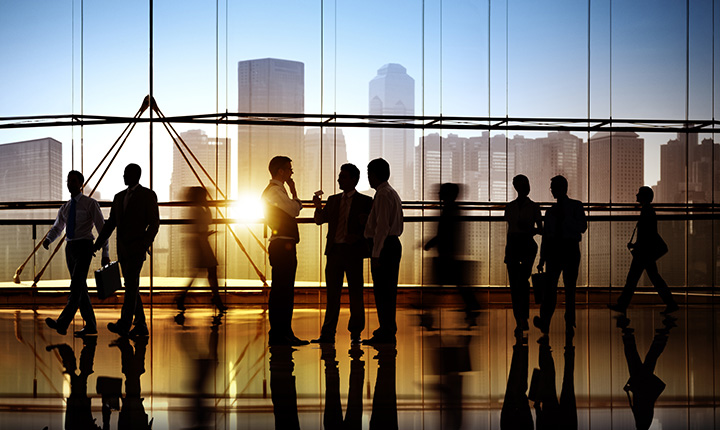 Silhouetted business people standing in front of a window with a sunset and a city scape in the background