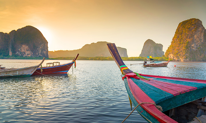 four colourful row boats sitting on the water with mountains and a sunset behind them
