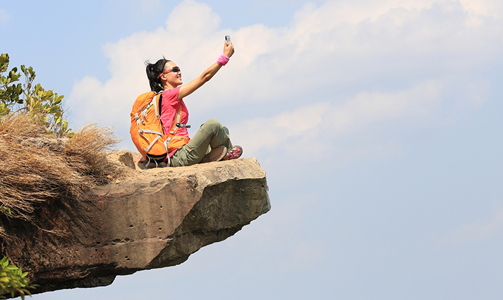 Hiker sitting on a rock cliff taking a photo with a phone
