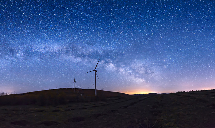 Starry night landscape with windmills on the horizon