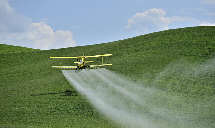 Crop-duster spraying pesticides on a field