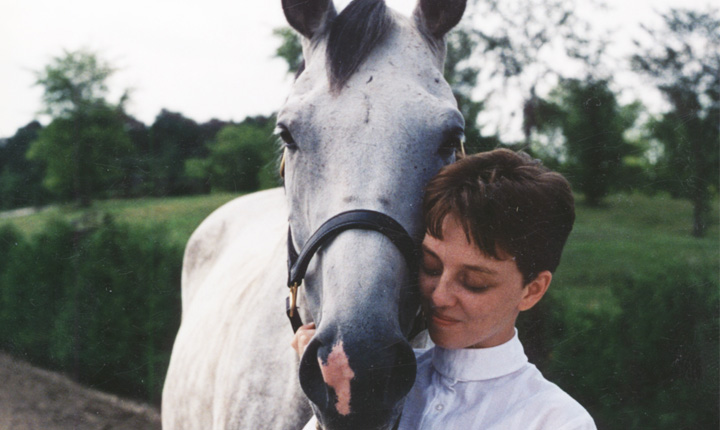 A woman wearing a white collared shirt with her face beside a grey horse.