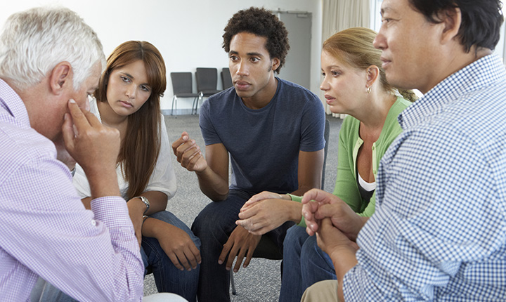 A diverse group of people sitting in a counselling session