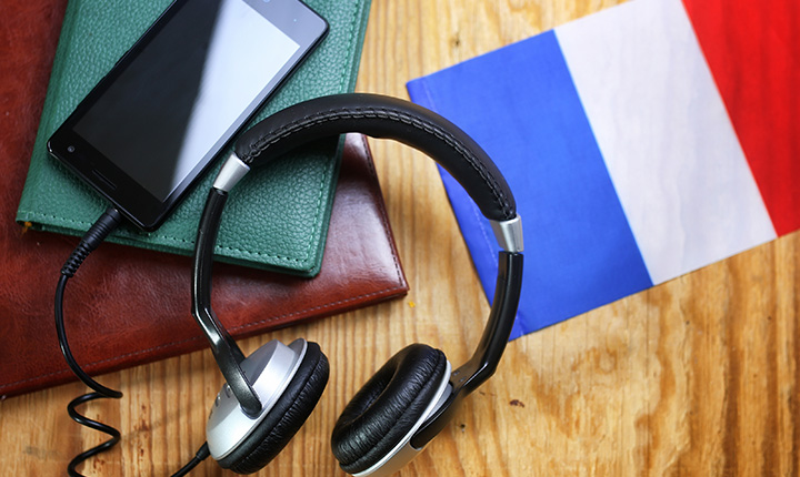Headphones, iphone resting on notebook with french flag on table