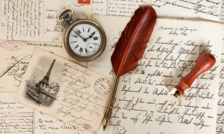 Notes with hand written messages with a feather pen and pocket watch sitting on top