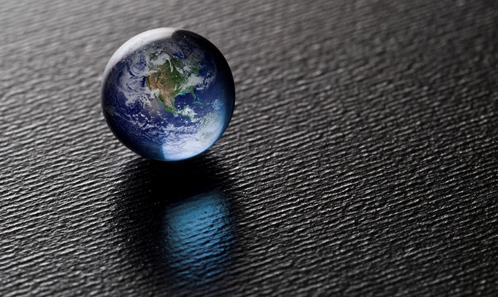 small glass globe reflected on black