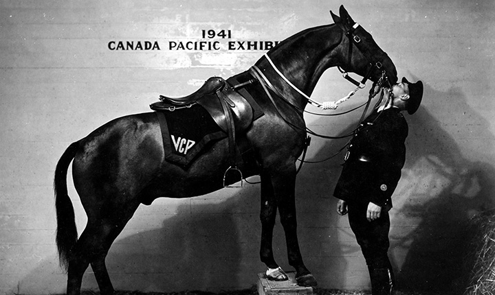 A black and white image of a horse kissing an officer