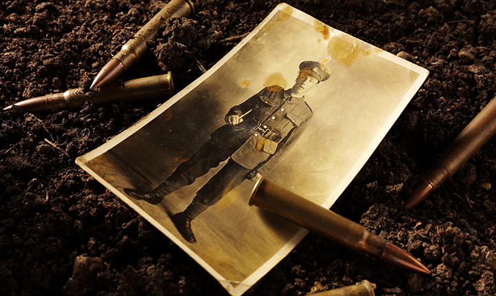 Sepia image of bullets and photo of soldier on ground