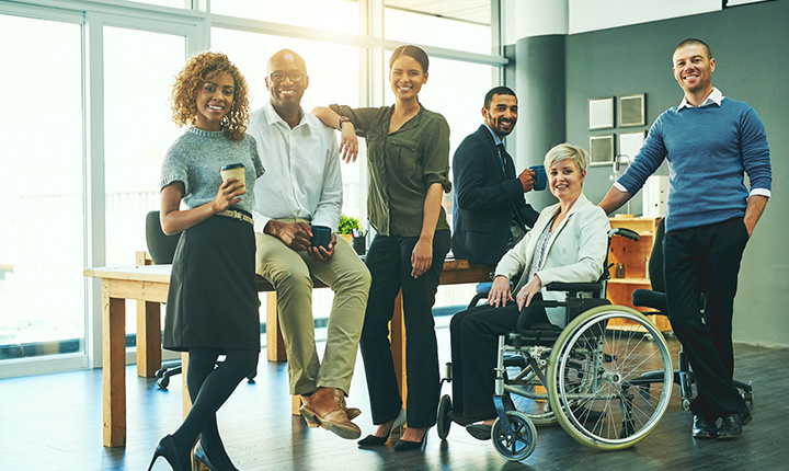 A group of people with a range of mobility standing in a sunny office