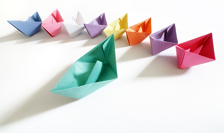 Colourful paper boats sitting in a line resembling leadership