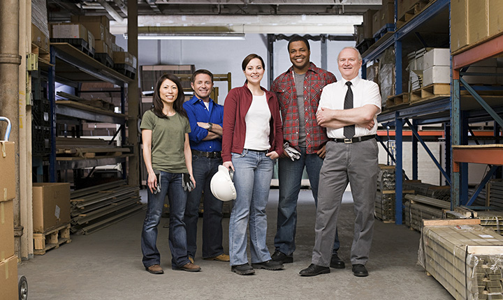 A diverse group of workers standing in front of a warehouse