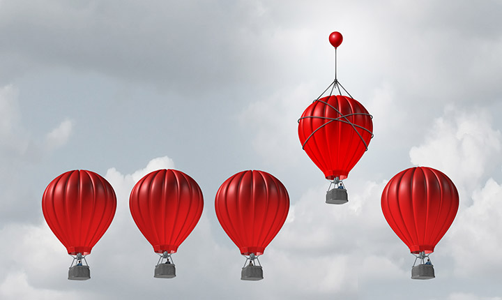 five red hot hair balloons floating in grey sky. one balloon higher than the rest.