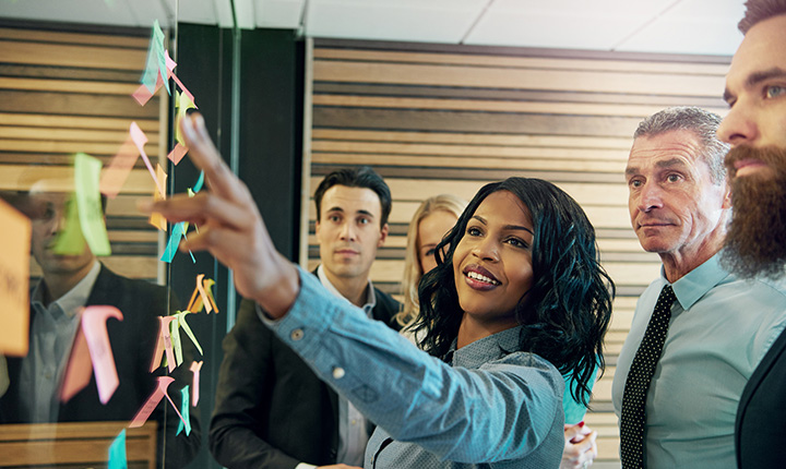 Woman explaining a plan to office team using sticky notes