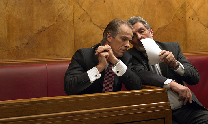 Two men in business suits whispering in court