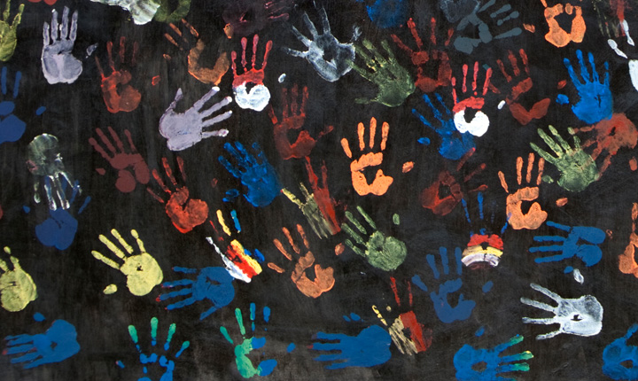 Hand prints in various paint colours on a black background