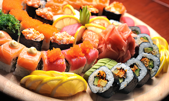 Plate of a variety of sushi, maki rolls and sashimi with lemon garnish