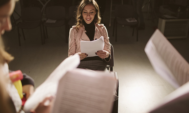 A woman sitting on a dark stage with a group of people reading scripts