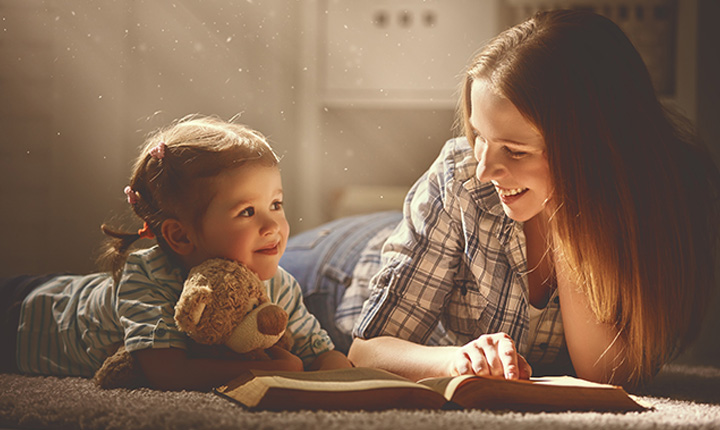 Woman and child laying on the floor reading a book with the sun shining on them
