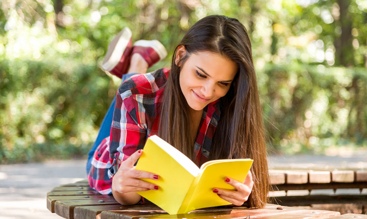 Young adult wearing a plaid shirt laying on a bench and reading a yellow book