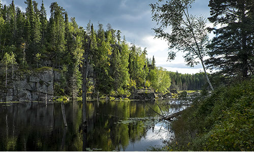 boreal forest river bounded by high cliffs